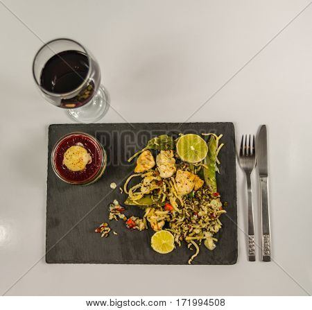 top wiev on a thai chicken with basmati rice coconut sauce on black stone plate with cutlerystrawberry dessert and red wine in a wineglass oriental food