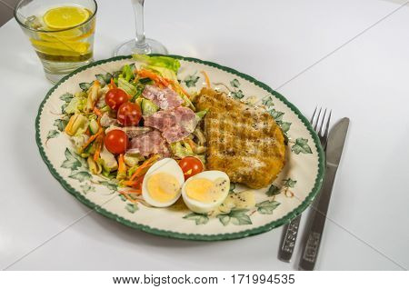 set with chicken bacon cherry tomatoes egg iceberg lettuce and a sauce water with lemon on a decorative plate