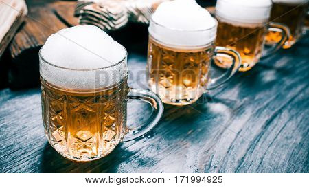 Glass mugs of beer or ale on rustic wood counter. Closeup wide view