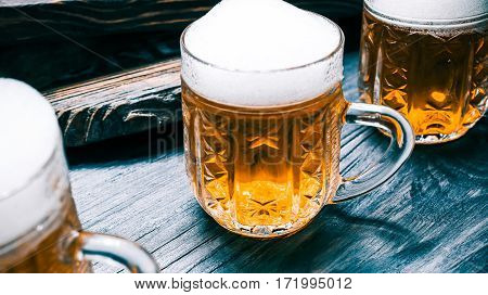 Golden beer or ale mugs on rustic wood. Closeup wide view