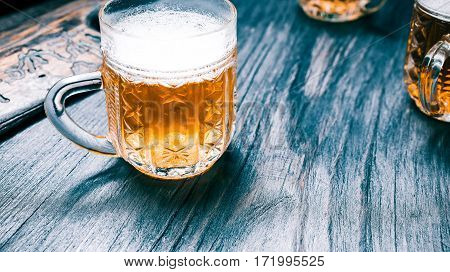 Mugs of beer or ale on rustic wood bar counter. Closeup wide view