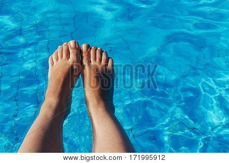 Naked Female Legs On A Background Of Blue Water