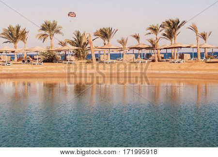 View Of The Lagoon, Sea, Beach, Palm Trees And A Parachute At Sunset