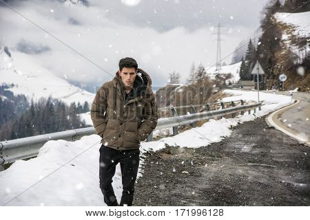 Young man walking on roadside under the snow up in the mountains. Snowy mountain on background