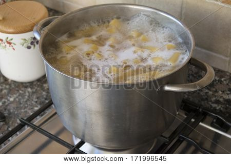 cooking of the rigatoni pasta in a metallic pot
