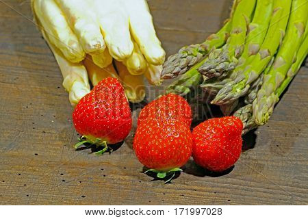 Freshly harvested asparagus and strawberries on a rustic old wooden board