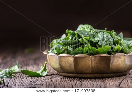 Spinach leaves.Fresh spinach leaves in retro bowl on oak wood board. Selective focus.