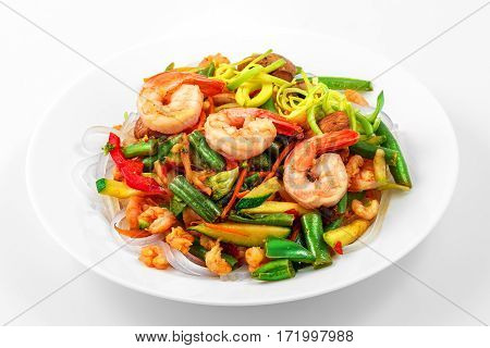 Warm salad with Funchoza, shrimp, fried vegetables, Funchoza, oyster sauce in a white plate on a white background