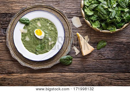 Spinach soup. Portion spinach soup with egg and cheese parmesan in retro style.