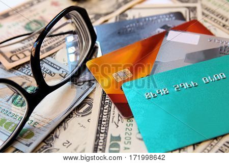 American dollars credit cards and eyeglasses close-up.