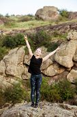 Young beautiful sportive girl smiling, showing peace, standing on rock in canyon. Copy space. poster