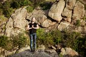 Beautiful sportive blonde girl practicing yoga asanas on rock in canyon. Copy space. poster