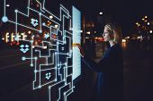 Young woman touching sensitive screen while selecting surface option. Female standing at big display with advanced innovative device with infographics design elements.Person with futuristic technology poster
