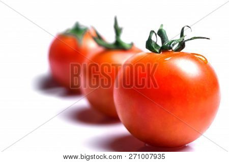 Close-up of fresh Red Tomatoes isolated on clean white Background.  Red Cherry Tomatoes with green Stem. Cocktail Tomatoes usable as decorative Background.