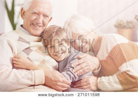 Loving grandparents spending time with smiling grandson poster