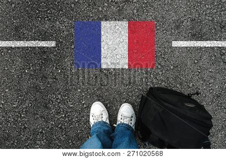 A Man With A Shoes And Backpack Is Standing On Asphalt Next To Flag Of France And Border