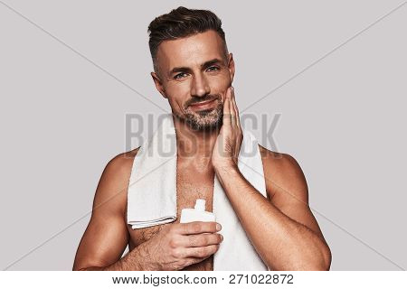 Confident In His Skin. Handsome Young Man Applying Aftershave Lotion And Smiling While Standing Agai