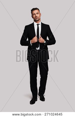 Confident Businessman. Full Length Of Handsome Young Man In Full Suit Adjusting His Jacket And Looki