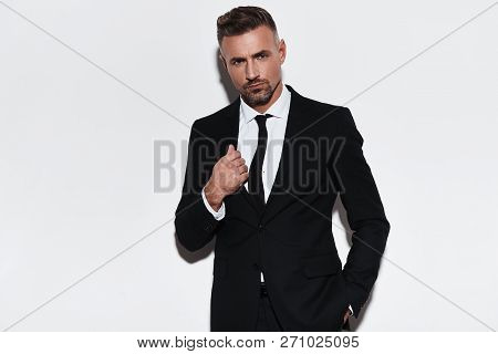 Confidence And Charisma. Handsome Young Man In Full Suit Adjusting Jacket And Looking At Camera Whil