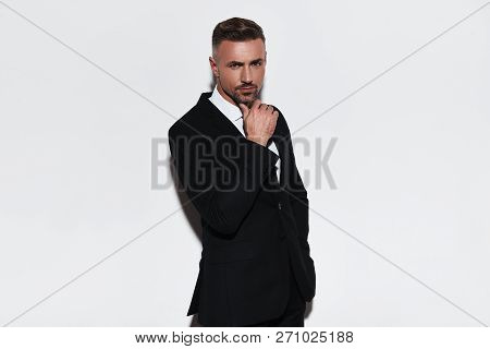 Confident Manager. Handsome Young Man In Full Suit Keeping Hand On Chin And Looking At Camera While