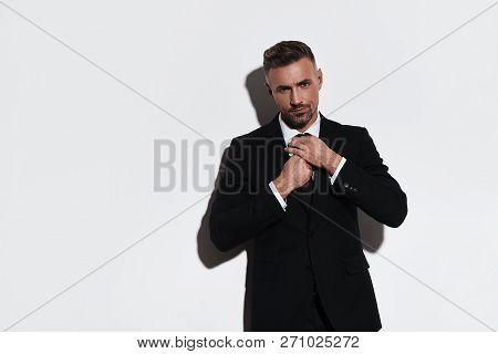 Confident Businessman. Handsome Young Man In Full Suit Adjusting Necktie And Looking At Camera While