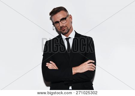 Confident Business Expert. Handsome Young Man In Full Suit Keeping Arms Crossed And Looking At Camer
