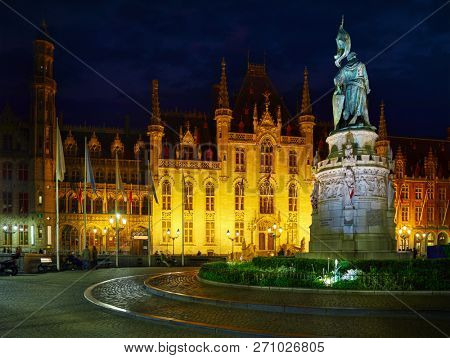 Bruges, Belgium. Central market square Grote Markt, historical centre with building of Provincial government and monument in honor of Jan Breydel Pieter De Coninck Nighttime panorama with street.