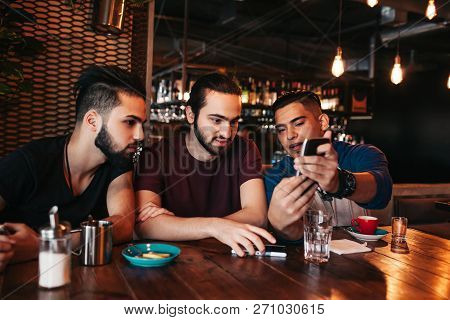 Group Of Mixed Race Young Men Talking And Using Phone In Lounge Bar. Multiracial Friends Having Fun