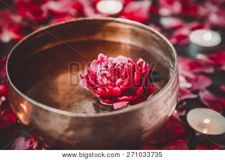 Tibetan Singing Bowl With Floating Inside In Water Red Peony Flower. Burning Candles And Petals On T