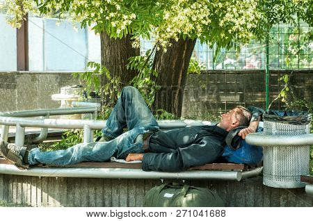 Homeless Veteran. Poor Hungry And Tired Homeless Man Ex Military Soldier Sleep In The Shade On The B