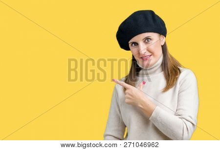 Middle age mature woman wearing winter sweater and beret over isolated background cheerful with a smile of face pointing with hand and finger up to the side with happy and natural expression on face