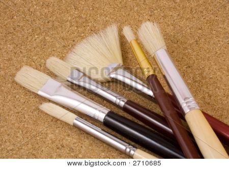 Collection of artist paint brushes laying on cork background poster