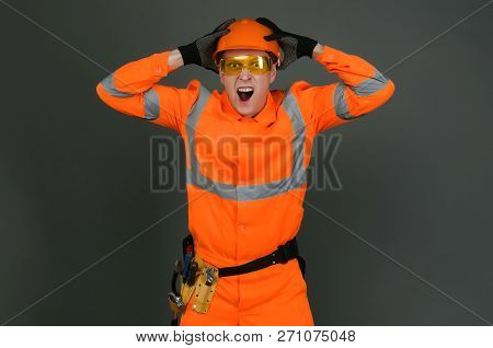 Shocked Builder Foreman In The Hardhat Is Holding His Head By His Hands Isolated On Gray Background.
