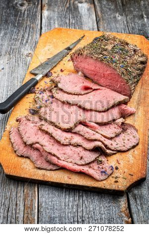 Traditional lunch meat with sliced cold cuts roast beef  as closeup on a cutting board