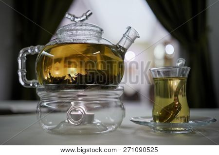 Transparent glass teapot on candle heater and glass teacup with teaspoon on table in cafe.
