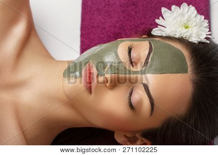 Woman With Clay Facial Mask   In Beauty Spa. Skincare. Beauty Concept. Close-up Portrait Of Beautifu