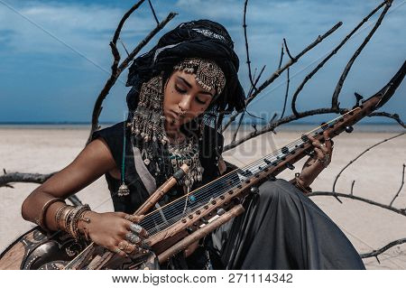Beautiful Young Stylish Tribal Woman In Oriental Costume Playing Sitar Outdoors