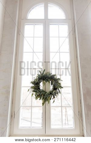Pretty Conifer Wreath Hanging On Huge Window During Christmas Celebration