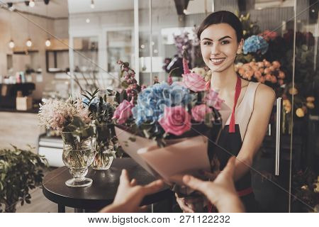 Beautiful Girl Florist Sends Bouquet To The Buyer. Smiling Young Girl Florist Giving A Bouquet Of Fl