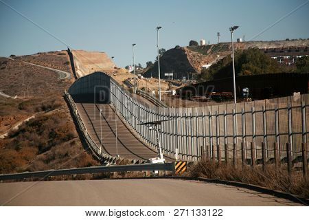 San Ysidro, California - 11/26/2018: The secured border fence and road for United States border patrol vehicles on the US - Mexico international border in California