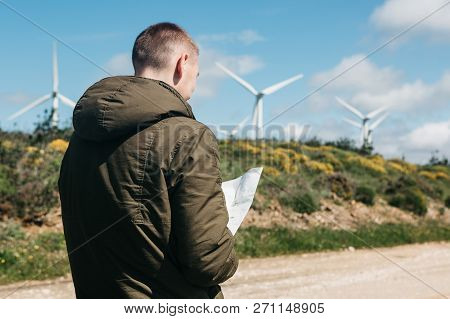 A Tourist Man Looks At The Map Of The Area For Further Travel. Unknown Terrain Or Unfamiliar Territo
