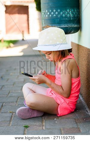 Girl Child Using Smartphone For Games Or Internet On Vacations. Little Girl Is Playing With Smartpho