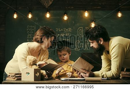 Homeschooling Concept. Father And Mother Reading Books, Teaching Their Son, Chalkboard On Background