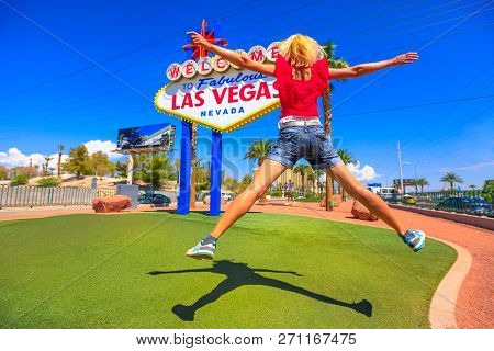 Young Woman Jumping At Welcome To Fabulous Las Vegas Nevada Sign, Popular Landmark On Las Vegas Stri