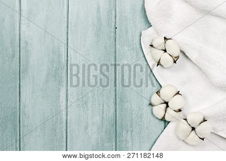 White Fluffy Towel With Cotton Boll Flowers Over A Blue Green Background. Image Shot From An Overhea