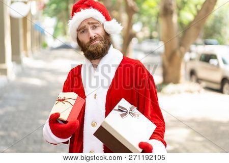 Puzzled Christmas Courier Carrying Gift Boxes. Bearded Young Man Wearing Santa Claus Costume Holding