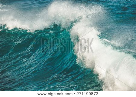 Close-up water clear turquoise splashing ocean wave. Bali. Perfect background for the different kinds of the collages and illustrations. Poerful breaking strength of wild virgin nature