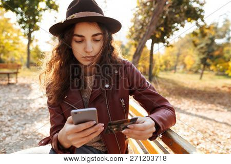 Pretty young girl sitting on a bench at the park, using mobile phone with credit card