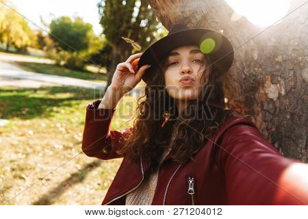 Image of a beautiful cute woman sitting in park take a selfie by camera.
