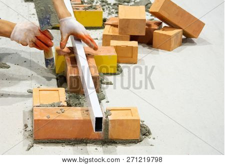 Bricklayer installing bricks, Bricklayer worker installing brick masonry on exterior wall with trowel putty knife poster